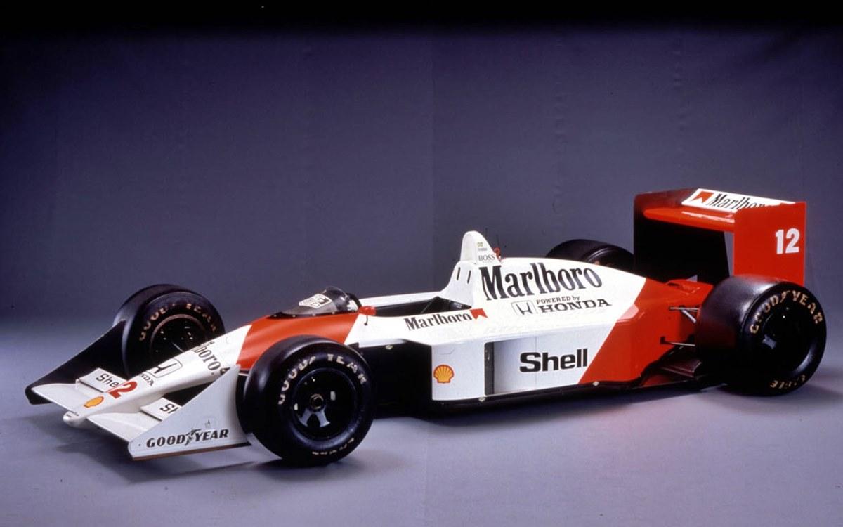 """El auto creado por Gordon Murray le permitió a McLaren, que tenía como pilotos a Ayrton Senna y Alain Prost, ganar 15 de las 16 carreras del torneo de 1988. Cansado de la lucha interna entre el inglés Nigel Mansell y el brasileño Nelson Piquet, Honda decidió dejar sorpresivamente al equipo Williams para la temporada 1988 de la Fórmula 1 y equipar con su buscado motor turbo de seis cilindros a McLaren, quien acababa de divorciarse de Porsche. Esta decisión marcó a la F.1 de aquellos años ya que derivó en un largo, agotador y extraordinario duelo entre el brasileño Ayrton Senna y el francés Alain Prost, una disputa dentro de la familia encabezada por el inglés Ron Dennis que forzó a los demás a ejercer el papel de actores de reparto. Ahora bien, ¿cómo se generó tal superioridad? Con el McLaren MP4/4-Honda. Pero para entender mejor el fenómeno de este vehículo hay que dar un paso atrás y viajar hasta mediados de la década de 1980. UN CONCEPTO INNOVADOR La adopción de los motores turbo, y la necesidad de montar radiadores e intercoolers cada vez más voluminosos, habían obligado a los diseñadores a levantar cada vez más el centro de gravedad de los coches. Hasta que en 1986 el sudafricano Gordon Murray, el brazo derecho del británico Bernie Ecclestone en Brabham, diseñó el modelo BT55. Para bajar el centro de gravedad del coche colocó el motor cuatro cilindros BMW """"acostado"""" con una inclinación a 72° en el lado izquierdo, mientras que hizo prácticamente desaparecer el habitáculo. El auto, teóricamente ganador, se convirtió en un fracaso debido a sus problemas estructurales (demasiada flexibilidad), mecánicos (motor poco fiable) y aerodinámicos (mala resolución de la aerodinámica posterior). Sin embargo, Murray no desistió con esta solución. Cuando llegó a McLaren, el técnico incorporó el concepto de monoplaza ultra-plano en el modelo MP4/4, que presentaba incluso una reducción adicional de la altura de los pontones laterales y una disposición diferente de los núcleos den"""